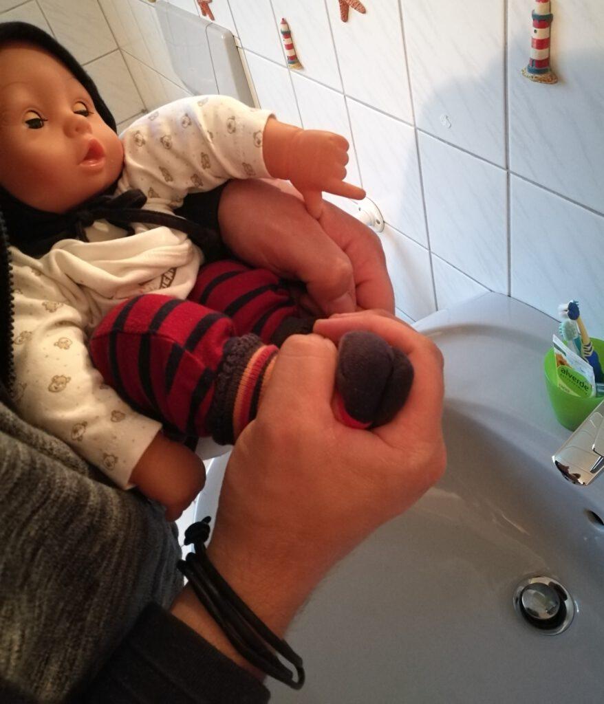 Baby wird über dem Waschbecken abgehalten