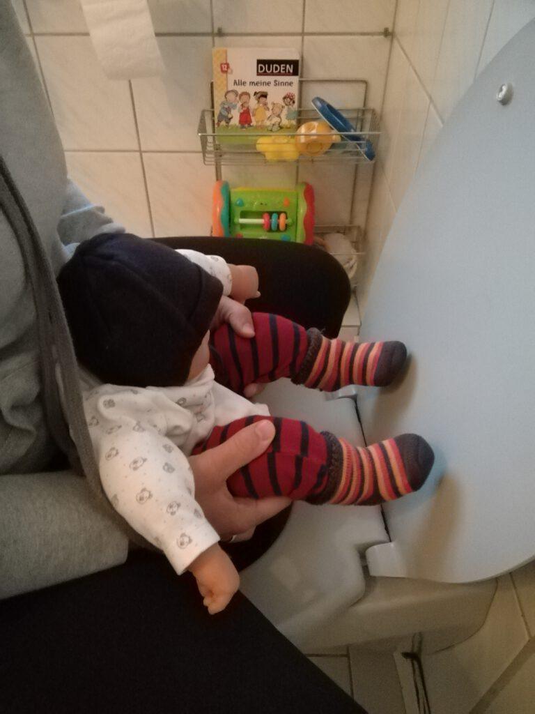 Abhalten rückwärts auf der Toilette